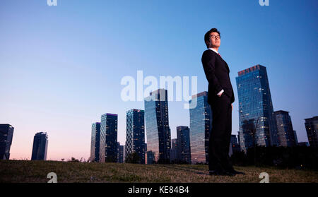 Businessman standing against buildings in city at night - Stock Image