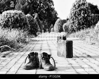 Leather boots in a foreground, in the middle of a brick road. A film camera on an antique suitcase, in a blurry background. Black-and-white photo. - Stock Image