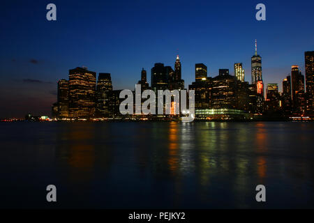 NEW YORK, NY - JULY 03: Financial District, Lower Manhattan skyline after sunset as seen from Brooklyn Bridge Park, Brooklyn - Stock Image