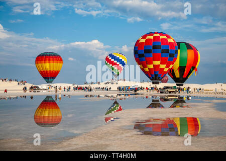 Hot air balloons reflected on puddle and people, White Sands Hot Air Balloon Invitational, White Sands National Monument, Alamogordo, New Mexico USA - Stock Image
