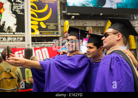 Manhattan, New York, U.S. - May 21, 2014 - In Times Square, three young men who graduated from New York University School of Business that day, are wearing purple graduation robes and black mortarboard hats, and taking Selfies photos with a cell phone in Manhattan. - Stock Image