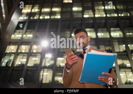Businessman with paperwork and smart phone below urban highrise at night - Stock Image