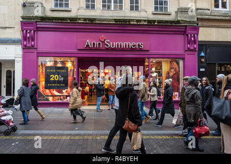 Shoppers walking past the front of the city of Bath Ann Summers shop with a  poster still in the window the  day after Black Friday - Stock Image