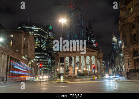 London, England, UK - December 17, 2018: Traffic passes the Bank of England and Royal Exchange buildings at Bank Junction, with skyscrapers of the Cit - Stock Image