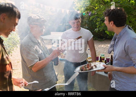 Male friends enjoying barbecue in backyard - Stock Image