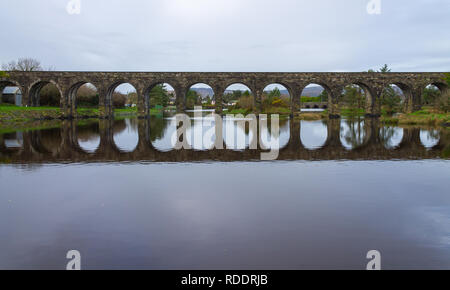 Ballydehob, West Cork, Ireland, January 18th 2019 A grey overcast day with intermittent drizzle and no wind allowed the old railway viaduct in Ballydehob to be almost perfectly reflected in the high tide waters.  Credit: aphperspective/Alamy Live News - Stock Image