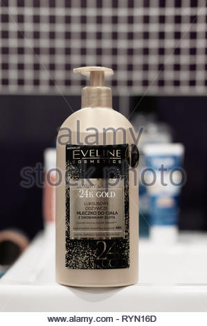 Poznan, Poland - March 8, 2019: Eveline Cosmetics 24K Gold body lotion in a plastic bottle. - Stock Image