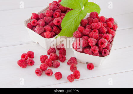 Fresh raspberries in cardboard boxes on a white wooden table - Stock Image