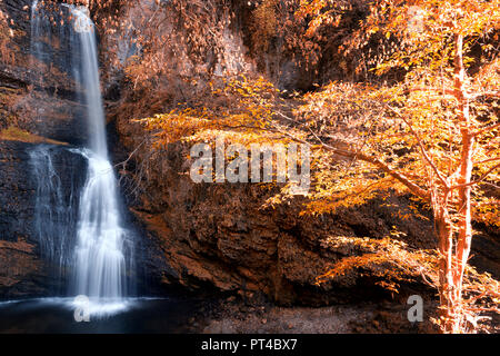 beautiful waterfall in woods in autumn season with sunny lights on the trees - Stock Image