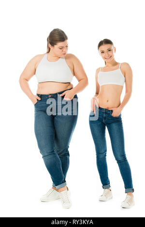 sad overweight woman jealously looking at smiling slim beautiful woman isolated on white - Stock Image