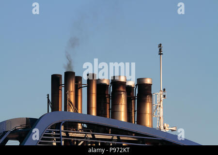 Smokestacks on a cruise ship emitting smoke while in harbour. Ships burning heavy fuel oil give rise to significant air pollution in harbour areas - Stock Image