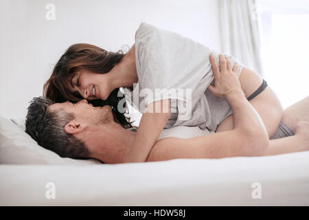 Intimate young couple looking at each other on bed. Romantic young couple on bed enjoying foreplay. - Stock Image