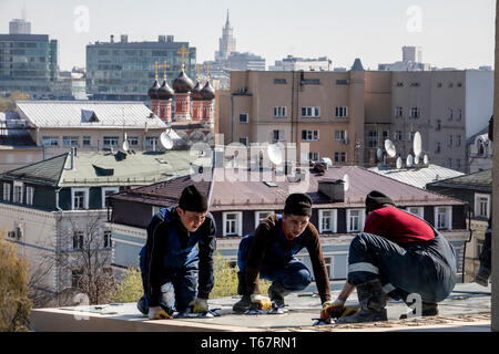 Workers from the republics of Central Asia repair the roof on an office building in the center of Moscow, Russia - Stock Image