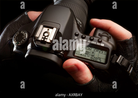Hands holding a digital SLR camera - Stock Image