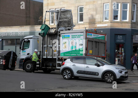 A green bin which has just emptied its contents into a bin lorry owned by Keenan Commercial Food Waste Collection Service - Stock Image