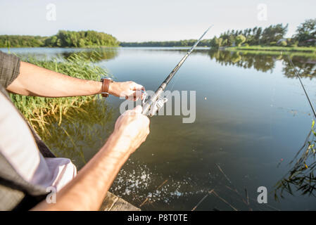 Fishing rod on the beautiful lake background during the morning light - Stock Image