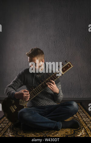 Portrait of a European man playing the sitar sitting on the carpet- Image - Stock Image