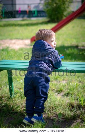 Young boy holding a toy locomotive and leaning on - Stock Image