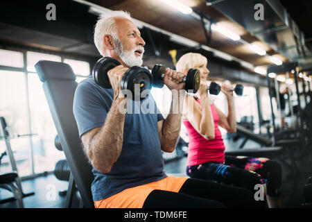 Happy senior people doing exercises in gym to stay fit - Stock Image