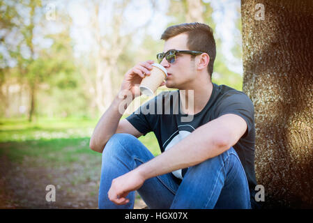 Young man sitting lonely in the park on a summers day - Stock Image