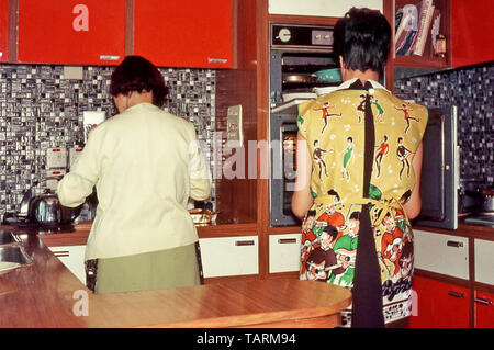 Archival back view of young housewife at oven & her Mum prepare food in new 1966 DIY kitchen interior Formica worktops mother and daughter England UK - Stock Image