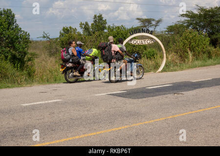 Two young travellers with backpacks on the back of motorcycle taxis draw up at a marker showing the equator line in western Uganda - Stock Image
