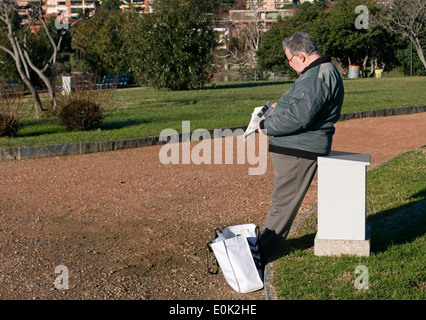 Man reading newspaper in the park, Switzerland - Stock Image