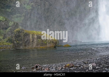 Rock dipped in water with waterfall in background - Stock Image