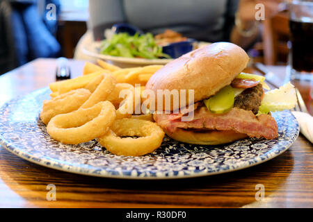 A JD Wetherspoons calorific Ultimate Burger meal served with onion rings and chips. high in calories and saturated fats. The meal is on a pub table - Stock Image