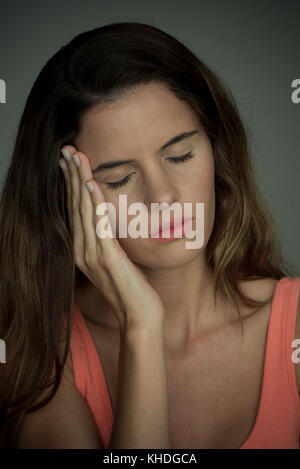 Young woman with hand on cheek, eyes closed - Stock Image