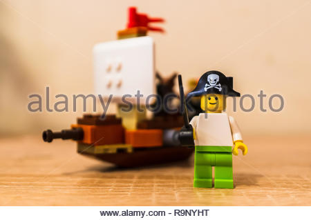 Poznan, Poland - December 26, 2018: Lego toy pirate holding a sword and standing in front of a ship in soft focus background. - Stock Image