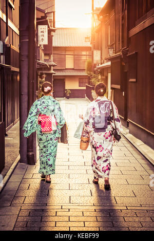 Two Japanese ladies wearing kimonos walking home into the sunset in Gion, Kyoto - Stock Image