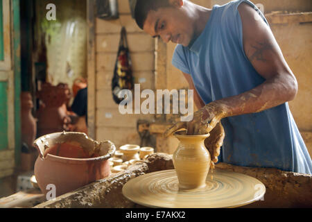Young Indo-Trini man (Ryan Lall) at a potter's wheel ,making a clay pots and deyas at Radika pottery in Chaguanas - Stock Image