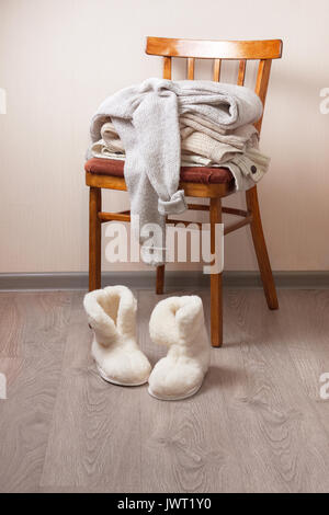 stack of warm clothes on the chair, Pair of warm winter sheepskin slippers - Stock Image