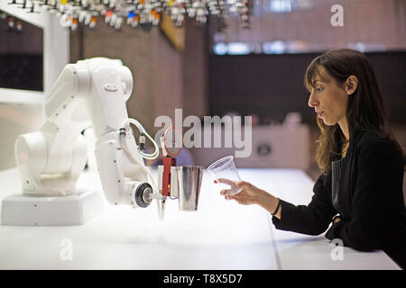 A women interacts with a robotic bartender called 'Makr Shakr' at a press preview for the 'AI: More Than Human' exhibition at the Barbican Centre in London. The major new exhibition explores the relationship between humans and artificial intelligence. - Stock Image