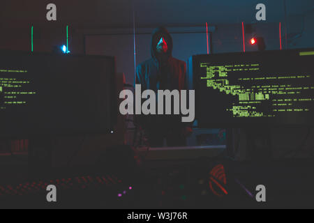 Serious bearded cyber-terrorist in hoodie standing in computer room with alarm system, computer monitors with codes on foreground - Stock Image