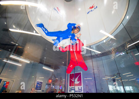 iFly wind tunnel indoor skydiving giving the participant the feeling of free falling weightless  pictured an instructor and child - Stock Image