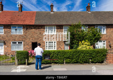 Young man standing outside the National Trust managed former home of former Beatles member, Paul McCartney, at Forthlin Road, Liverpool. - Stock Image