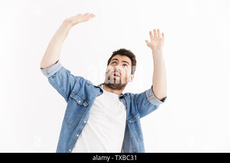 Portrait of a scared handsome bearded man wearing casual clothes standing isolated over white background, covers himself with hands - Stock Image