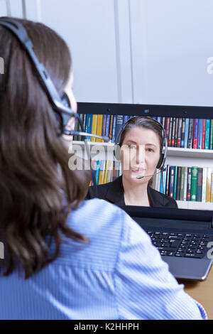 Rear view of a woman in a blue blouse with headset and laptop, making a live video call with the female head of the human resources department, online - Stock Image