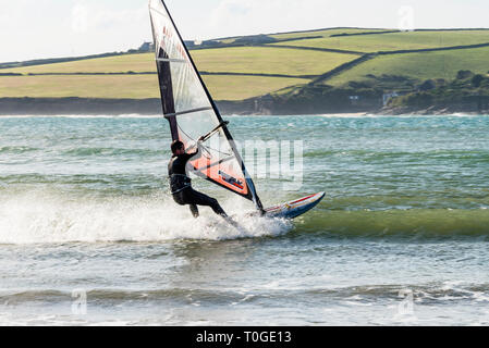 Male windsurfer skimming the waves at the mouth of the estuary. - Stock Image
