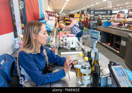 Female check-out counter worker in Aldi Supermarket, Gogmore Lane, Chertsey, Surrey, England, United Kingdom - Stock Image