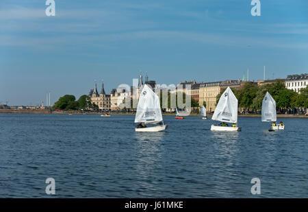 Junior sailors in optimist dinghies on the Peblinge Lake in central Copenhagen. View towards Søtorvet and Dronning - Stock Image