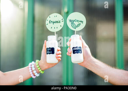 Holding bottles with almond and oat milk with stickers on the green background - Stock Image