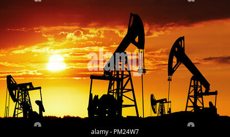 Oil pumps silhouette at colorful sunset - Stock Image