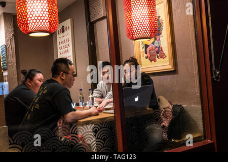Oriental group of four 25-35 years in a Chinatown Chinese restaurant sitting around a table reviewing screen information on an Apple MacBook computer Soho West End Chinatown London UK - Stock Image