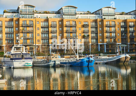 Boats reflected in the waters of regenerated St Katherines Dock in London. - Stock Image