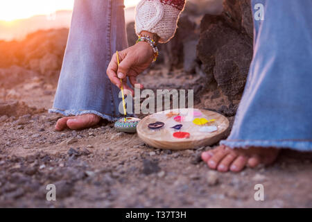 Alternative hippy barefoot style caucasian woman painting mandala on stones on the ground - feeling with nature and outdoor leisure activity - sunset  - Stock Image