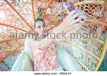 Young woman taking selfie while sitting on spherical chair - Stock Image