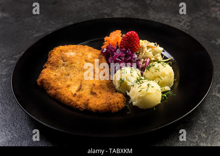 Pork meat served with potato and salad on plate. - Stock Image